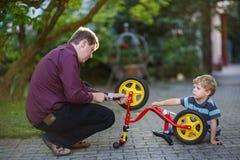 Мальчик и его отец ремонтируя колесо велосипеда outdoors. Стоковая Фотография
