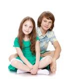 Мальчик и его сестра сидя на поле Стоковая Фотография