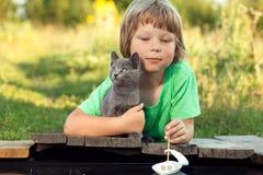 Мальчик и его любимый котенок играя с шлюпкой от пристани в пруде стоковые фотографии rf