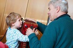 Мальчик и дед маленького ребенка играя аппаратуру музыки стоковое изображение rf