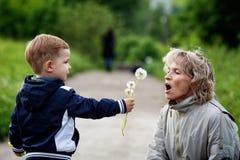 Мальчик и женщина с одуванчиком Стоковые Фото