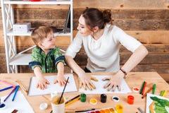 Мальчик и мать делая печати из покрашенных рук на бумаге Стоковая Фотография RF