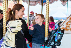 Мальчик и мать на Carousel усмехаясь на одине другого Стоковые Фото
