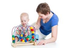 Мальчик и мать ребенка играют с игрушкой цвета воспитательной стоковое изображение