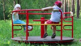 Мальчик и маленькая девочка едут карусель в зеленом лесе на летнем дне сток-видео