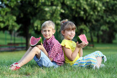 Мальчик и маленькая девочка едят арбуз Стоковое Изображение