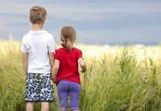 Мальчик и маленькая девочка стоя держащ руки смотря на hor Стоковое Изображение