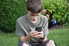 Мальчик и мобильный телефон Стоковая Фотография RF