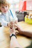 Мальчик и отец держа стекло milkshake совместно в кафе Стоковое Изображение RF