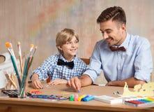 Мальчик и папа крася совместно стоковые фото