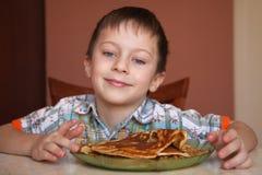 Мальчик и плита с блинчиками стоковые изображения