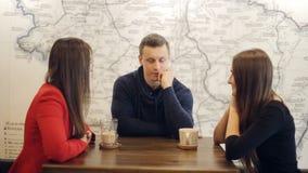 Мальчик и 2 смеяться над и беседы девушек в кафе видеоматериал