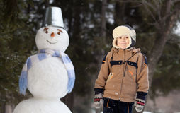 Мальчик и снеговик Стоковые Фотографии RF