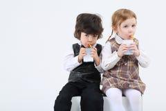 Мальчик и усаживание и питье девушки сок Стоковая Фотография