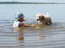 Мальчик и щенок играя в реке Стоковое фото RF