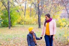 Мальчик идя с его матерью в парке осени стоковые фотографии rf