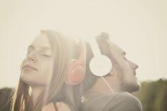 Мальчик и girll слушая к музыке Стоковые Фотографии RF