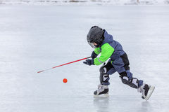 Мальчик катаясь на коньках и играя хоккей Стоковое Изображение