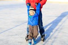 Мальчик катаясь на коньках с родителем Стоковое фото RF