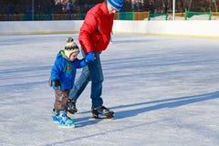 Мальчик катаясь на коньках с родителем Стоковое Изображение