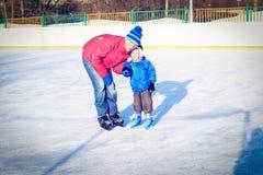 Мальчик катаясь на коньках с родителем Стоковая Фотография