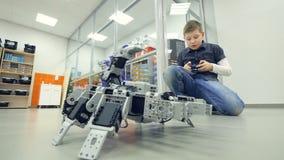 Мальчик контролируя скорпиона робота кнюппелем 4K акции видеоматериалы