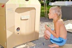 Мальчик красит картонную коробку Стоковые Фотографии RF