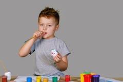 Мальчик крася пасхальное яйцо Стоковое фото RF