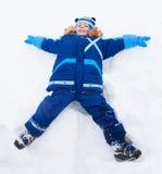 Мальчик кладя в форму звезды в снеге Стоковая Фотография