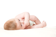 Мальчик кладя на одеяло играя с его рукой Стоковая Фотография RF