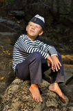 Мальчик матроса сидя на камне Стоковые Изображения RF