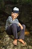 Мальчик матроса сидя на камне Стоковое Фото