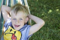 Мальчик маленького милого ребенка белокурый отбрасывая и ослабляя на гамаке Стоковое Фото
