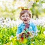 Мальчик маленького ребенка есть зайчика пасхи шоколада Стоковая Фотография