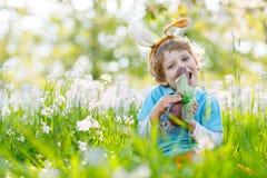 Мальчик маленького ребенка есть зайчика пасхи шоколада Стоковые Фотографии RF