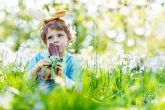 Мальчик маленького ребенка есть зайчика пасхи шоколада outdoors Стоковые Фотографии RF
