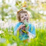 Мальчик маленького ребенка есть зайчика пасхи шоколада outdoors Стоковые Изображения RF