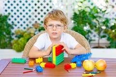 Мальчик маленького ребенка играя с красочными пластичными блоками Стоковая Фотография RF