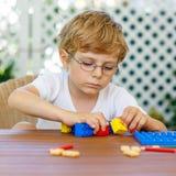 Мальчик маленького ребенка играя с пластичными блоками Стоковые Фотографии RF