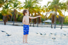Мальчик маленького ребенка имея потеху на тропическом пляже Стоковые Изображения