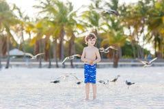 Мальчик маленького ребенка имея потеху на тропическом пляже Стоковая Фотография RF