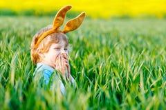 Мальчик маленького ребенка имея потеху с традиционной охотой пасхального яйца Стоковое Изображение