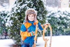 Мальчик маленького ребенка наслаждаясь ездой саней в зиме стоковые фото