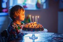 Мальчик маленького ребенка празднуя его день рождения и дуя свечи на торте Стоковые Фото