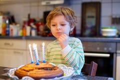 Мальчик маленького ребенка празднуя его день рождения и дуя свечи на торте Стоковое Изображение RF