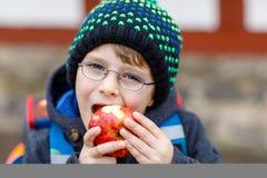 Мальчик маленького ребенка с стеклами глаза идя от школы и есть яблоко Стоковые Фотографии RF