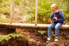 Мальчик малыша сидя самостоятельно на деревянном мосте в лесе Стоковая Фотография RF