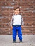 Мальчик малыша смеяться над кирпичной стены Стоковые Изображения RF