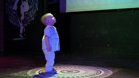 Мальчик малыша стоя в середине сцены и floodlit Милый ребенок рассматривает клуб и освещение видеоматериал