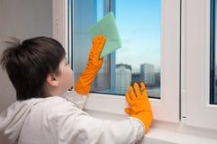 Мальчик моет окно стоковая фотография